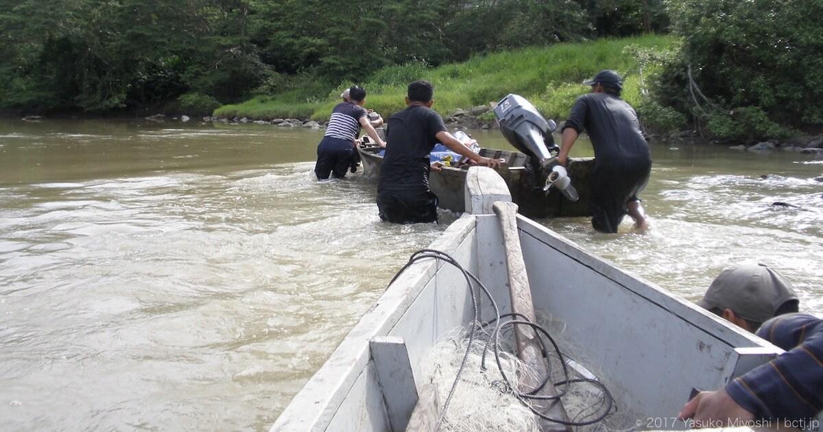 時には川の中でボートを押して進む